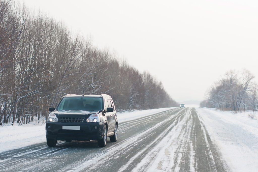 Black car on a winter road with winter tires